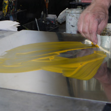 <p>Drucker Detlef Jäger beim Auftragen der Farbe auf eine Radierplatte</p>
